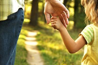 kind houdt hand vader vast