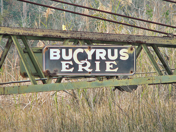 Decades old Bucyrus Erie logo laying at waters edge in Moss Point  Mississippi