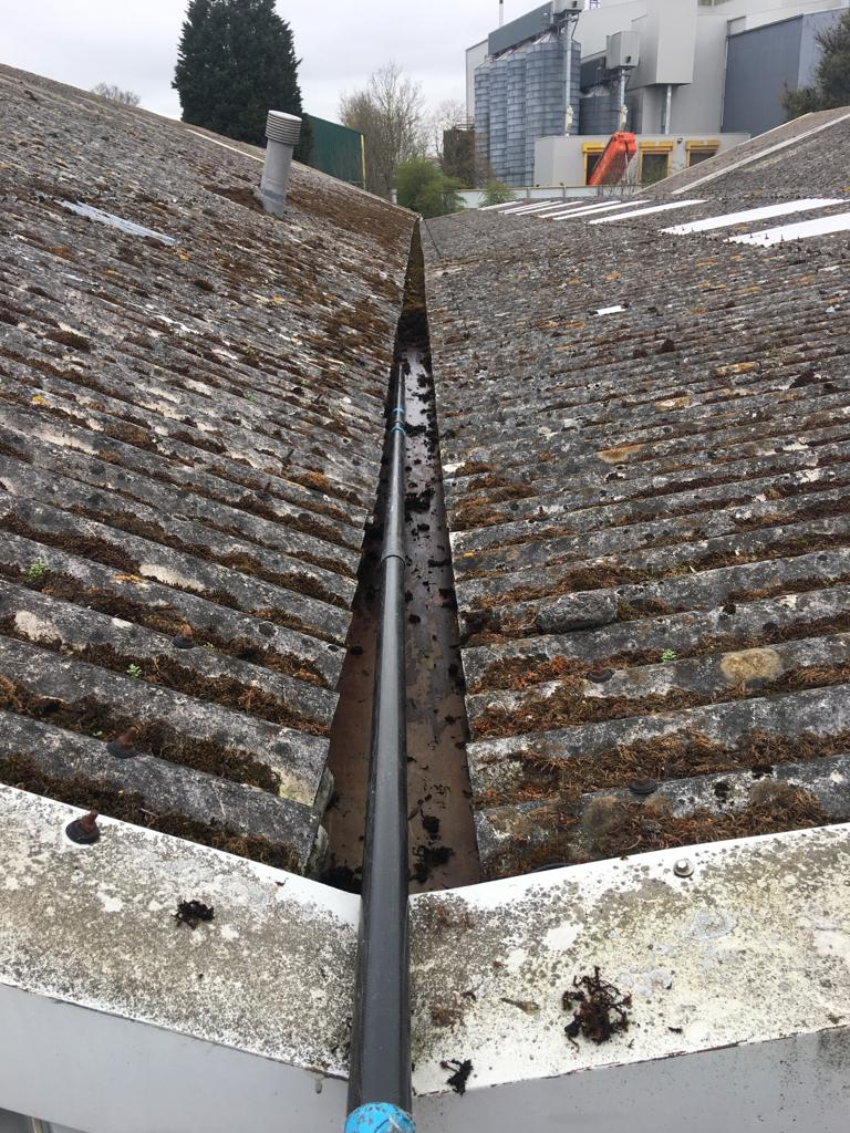 Gutter clearing on industrial gutter using a gutter vacuum