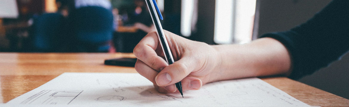 A human hand writing using a pen