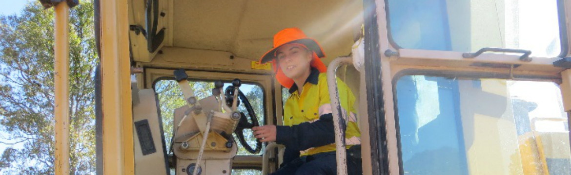 A young woman driving a construction vehicle