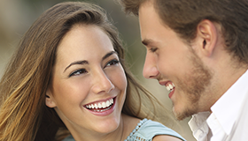 Picture of a young couple with big smiles talking
