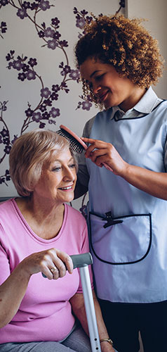 Caregiver helping senior brush her hair