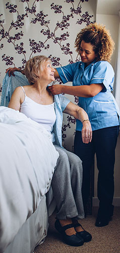 picture of caregiver helping senior getting dressed
