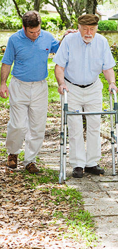 Caregiver walking with senior who is using a walker