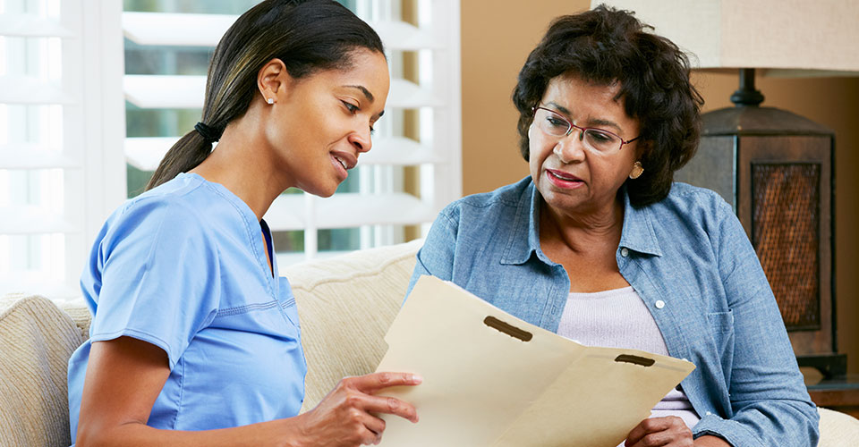 Caregiver reviewing senior's file with senior's daughter