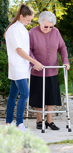Caregiver assisting senior with walker