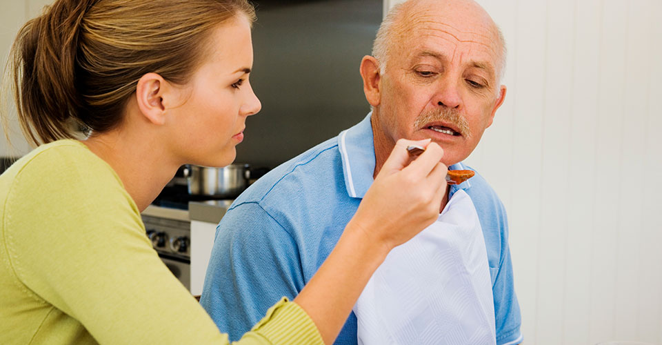 picture of caregiver feeding senior