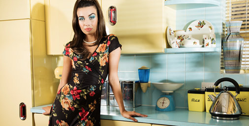 Model in kitchen wearing black floral dress by 'Voodoo Vixen' leans on worktop