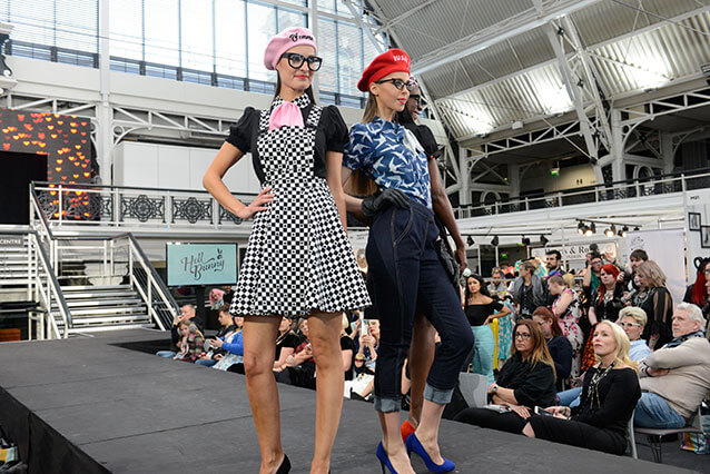 Fashion buyers watch three models posing on catwalk