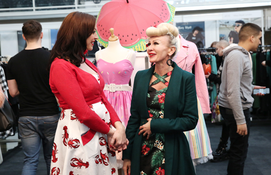 Exhibitor wearing red cardigan and lobster patterned skirt talks to a buyer
