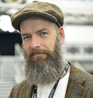 Man in brown tweed jacket and flat cap smiling at camera
