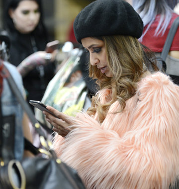 Young fashion buyer using mobile phone at LondonEdge Trade Show