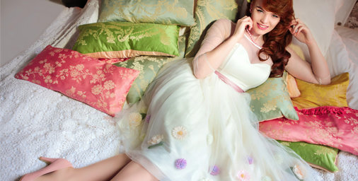 model with red hair and wearing 'Collectif' white skirt and top, lyling on coloured cushions