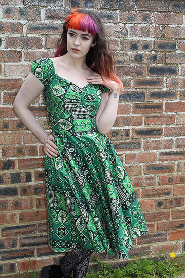 Model with red highlighted hair poses in fron of birck wall in a green patterned dress