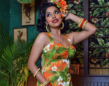 Dark haired model with hand on side of head, wearing flower and leaf designed dress