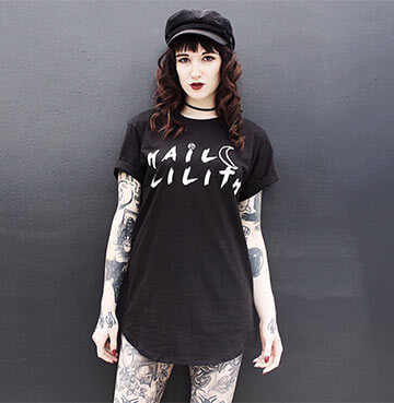tattooed women wearing long black t-shirt and flat black cap