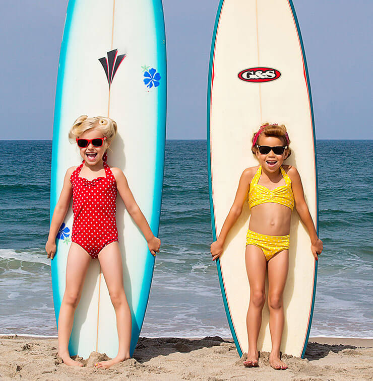 Girl's on beach standing in front of surf boards, wearing sunglasses and 'Red Dolly' swimwear