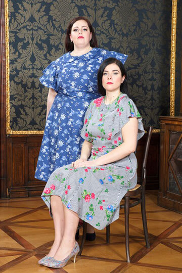 Two female models posing wearing patterned dresses