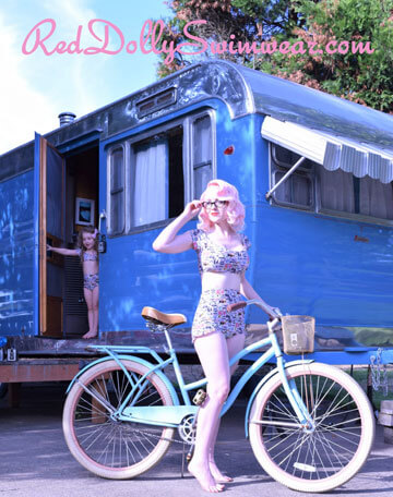 Vintage picture of young women on bicycle, in front of blue caravan