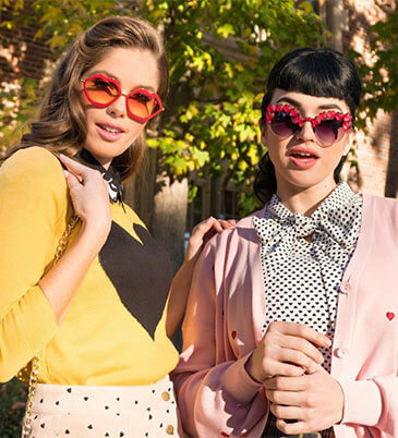 Models posing in yellow and pink vintage tops