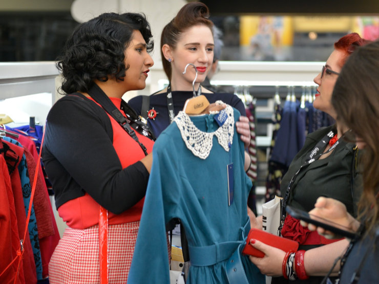 Exhibitor showing clothing to buyer