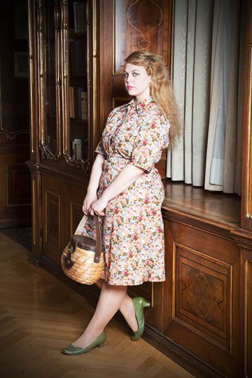 Female model leaning against wood panelled window wearing brightly coloured  patterned dress holding handbag