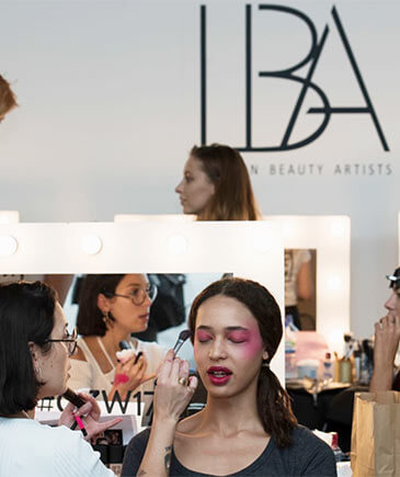 Artist applying make-up to model at fashion show