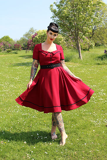 Model in field wearing red dress by Sheen Clothing