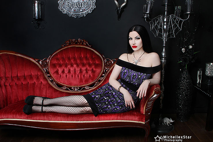 Goth chic in purple and black banded dress , lying on Victorian  chaise longue sofa