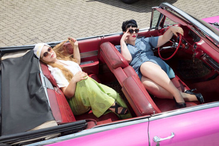 Two female models in old pink American car, wearing vintage fashion clothing