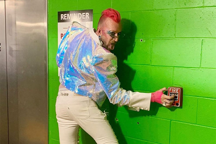 Sequins Blog - Man with red mohican, wearting sequin jacket  pressing fire escape button