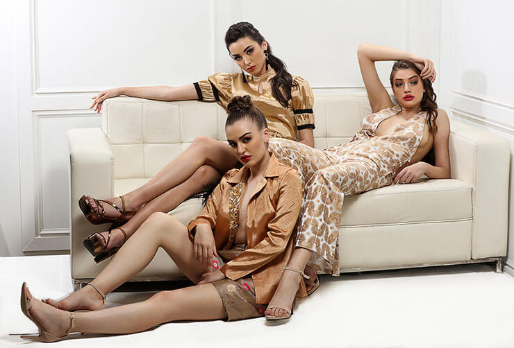 Three models lying on sofa wearing Aesavaali party outfits