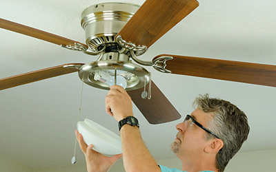 Electrician servicing a ceiling fan and light