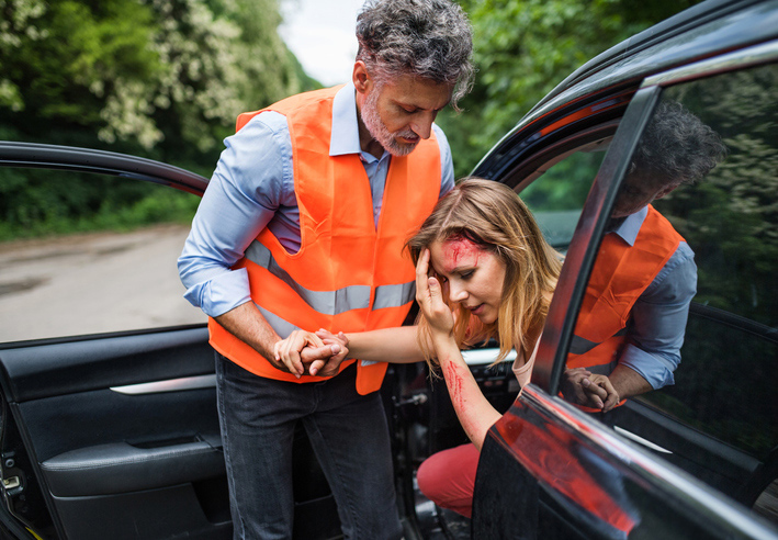 A woman with injuries exiting a vehicle involved in an accident