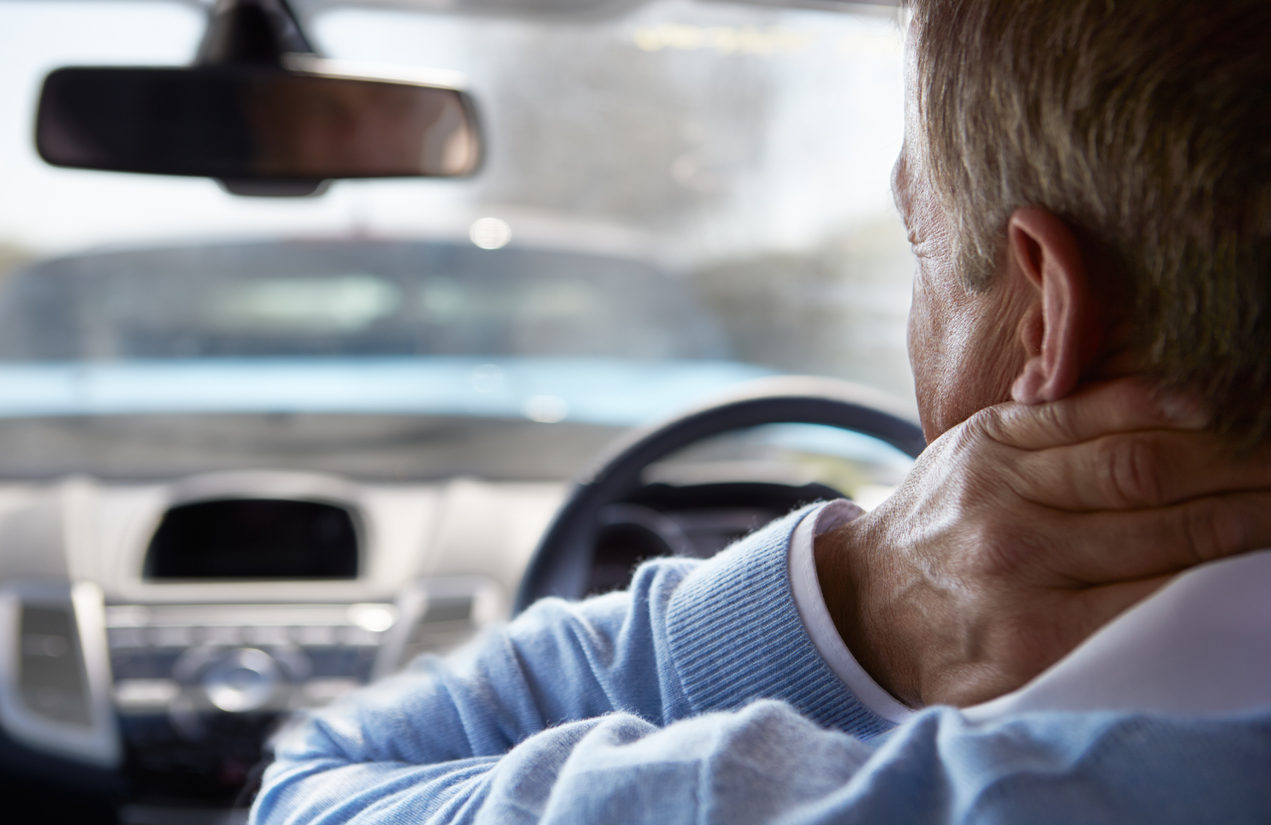 A man showing pain in his neck after a car crash