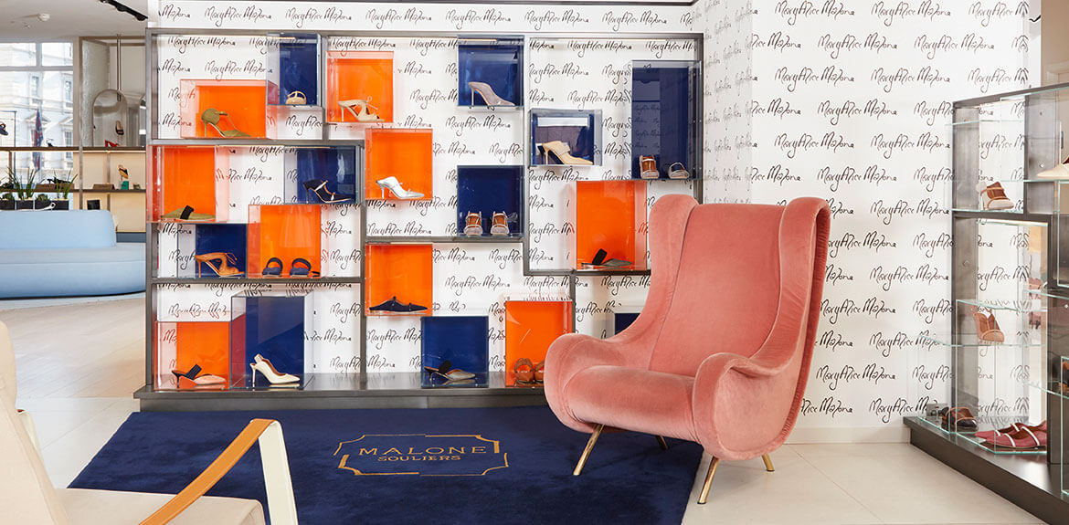 Malone Souliers red and blue display wall with 'Mary Alice Malone' signature wallpaper