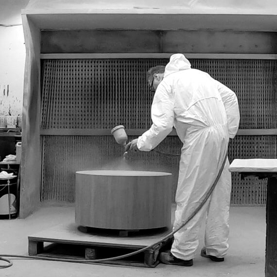 Man  in protective clothing, spraying  wooden table