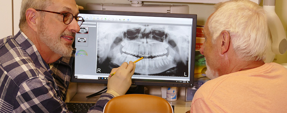 Dentist reviewing digital x-ray with patient