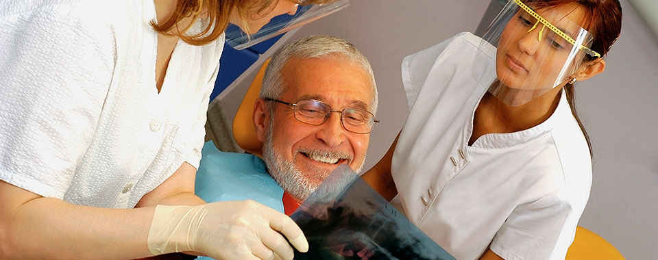 Older male patient reviewing exam results with dentist and hygienist